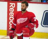 Kyle Quincey kneels in front of the bench during pre-game warmups.