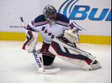 Henrik Lundqvist of the New York Rangers stretches near the boards during pre-game warmups before a game against the Detroit Red Wings.