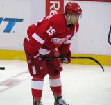 Riley Sheahan crouches near center ice during pre-game warmups.