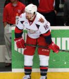 Xavier Ouellet crouches near the open bench door at the end of pre-game warmups before a Grand Rapids Griffins game.