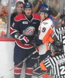 Vili Saarijarvi of the Firebirds and Greg DiTomaso of the Spirit come together along the boards on the outside of a scrum between Flint and Saginaw.