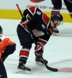 Brady Gilmour of the Saginaw Spirit lines up for a faceoff in a game against the Flint Firebirds.