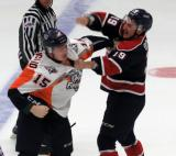 Vincent Scognamiglio of the Flint Firebirds and Connor Brown of the Saginaw Spirit fight in the neutral zone.
