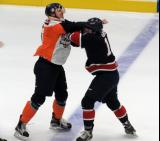 Vincent Scognamiglio of the Flint Firebirds and Connor Brown of the Saginaw Spirit swing away at each other during a first-period fight.