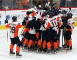 Will Bitten of the Flint Firebirds jumps onto a group of his teammates as they celebrate the team's shootout win in their inaugural home opener.