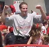 "Steve Duchesne flexes his muscles in a ""strong man"" pose during the parade honoring the Red Wings' 2002 Stanley Cup Championship."
