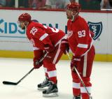Mike Green and Johan Franzen stand near the boards during pre-game warmups.