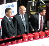Detroit assistant coaches Chris Chelios, Pat Ferschweiler, and Tony Granato stand on the bench during introductions at the Red Wings' home opener.