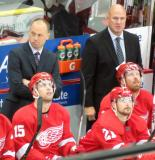 Red Wings' head coach Jeff Blashill and assistant coach Pat Ferschweiler stand at the bench behind Riley Sheahan, Tomas Tatar, and Johan Franzen.