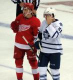 Dylan Larkin stands next to Toronto's Jake Gardiner during a stop in play.