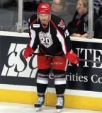 Brian Lashoff crouches at the boards during pre-game warmups before a Grand Rapids Griffins game.