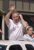 Former Red Wing Mickey Redmond waves to the fans while taking on a cell phone during the parade honoring the Red Wings' 2002 Stanley Cup Championship.