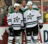 Patrick Sharp and Jason Spezza of the Dallas Stars stand at the boards during pre-game warmups before a game against the Detroit Red Wings.
