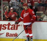 Mike Green hands a puck through the glass to a kid during pre-game warmups.