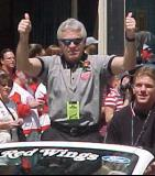 "Associate Coach Barry Smith gives the ""thumbs up"" sign to fans during the parade honoring the Red Wings' 2002 Stanley Cup Championship."