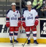 Andy Miele and Nick Jensen stand at the boards during pre-game warmups before the Grand Rapids Griffins' Purple Game.