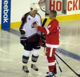Valeri Kamensky and Igor Larionov talk while standing in the neutral zone prior to the start of the second period of the 2016 Stadium Series Alumni Game at Coors Field.