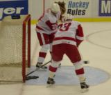 Stacy Roest and Kris Draper clear pucks out of the net during pregame warmups before a preseason game.