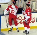 Darren Helm and Dylan Larkin stand at the bench during pre-game warmups prior to the Stadium Series game in Denver.