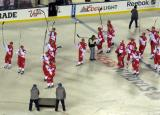 The Detroit Red Wings raise their sticks to salute their fans after the Stadium Series game in Denver.