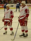 Jason Williams and Maxim Kuznetsov stand inside the blue line during pregame warmups before a preseason game.
