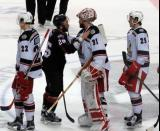 Jaime Sifers of the Lake Erie Monsters talks to Jared Coreau of the Grand Rapids Griffins during the handshake line, with Louis-Marc Aubry and Evgeny Svechnikov on either side of them.
