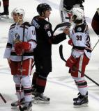 Tyler Bertuzzi of the Grand Rapids Griffins and Zach Werenski of the Lake Erie Monsters talk during the handshake line with Tomas Nosek next to them.