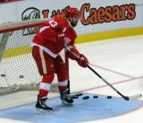Darren Helm clears pucks out of the net during pre-game warmups before a preseason game.