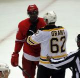 Givani Smith is held back by Alex Grant of the Boston Bruins during a stop in a preseason game.