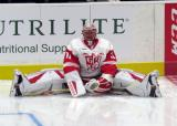 Jared Coreau stretches on the ice near the boards during pre-game warmups before a Grand Rapids Griffins game.