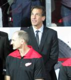 Chris Chelios stands at the bench after being introduced as an assistant coach during the Red Wings' home opener.