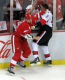 Jonathan Ericsson and Dion Phaneuf of the Ottawa Senators grapple with each other in a fight near the boards.