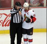 Erik Karlsson of the Ottawa Senators talks with linesman Lonnie Cameron during a stop in play of a game against the Detroit Red Wings.
