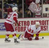 Luc Robitaille skates over to Jesse Wallin as Wallin stretches during pregame warmups.