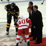 Henrik Zetterberg and Boston Bruins' captain Zdeno Chara take a ceremonial faceoff with the puck dropped by former Red Wings Joe Kocur, Kris Draper, and Kirk Maltby.