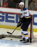 Kevin Shattenkirk of the St. Louis Blues clears pucks out of the net during pre-game warmups before a game against the Detroit Red Wings.