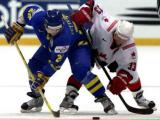 Henrik Zetterberg, playing for Team Sweden, fights for the puck with Kris Draper, playing for Team Canada, during the gold medal match at the 2003 World Championship.