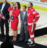 Henrik Zetterberg stands with wife Emma, son Love, and Red Wings legend Ted Lindsay during a pre-game ceremony honoring Zetterberg for his 1000th career game.