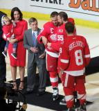 Henrik Zetterberg, alongside wife Emma, son Love, and Red Wings legend Ted Lindsay, accepts a gift from his teammates represented by Niklas Kronwall and Justin Abdelkader, during a pre-game ceremony honoring Zetterberg for his 1000th career game.