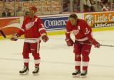 Chris Chelios and a Derian Hatcher stand just inside the blue line during pregame warmups before a preseason game.