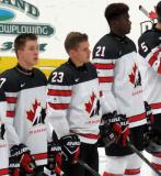 Taylor Raddysh, Sam Steel, and Givani Smith of Team Canada stand at the blue line for the playing of the national anthems before a game against Team USA at the 2017 World Junior Summer Showcase.