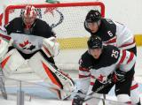 Carter Hart, Logan Stanley, and Robert Thomas of Team Canada get set for a faceoff during a game against Team USA at the 2017 World Junior Summer Showcase.