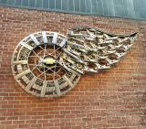 A winged wheel sculpture on the wall near the northeast exit at Little Caesars Arena.