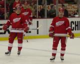 Three defensemen - Niklas Kronwall, Chris Chelios (background) and Mathieu Schneider - stand near the blue line during pregame warmups.
