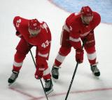 Darren Helm and Nick Jensen of the Detroit Red Wings get set for a faceoff during a preseason game against the Boston Bruins.