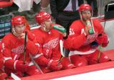 Gustav Nyquist, P.A. Parenteau, and Frans Nielsen of the Detroit Red Wings sit on the bench during a preseason game against the Boston Bruins.