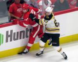 Jakub Zboril of the Boston Bruins puts David Booth of the Detroit Red Wings into the boards during a preseason game.