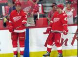 Anthony Mantha and Darren Helm of the Detroit Red Wings stand at the boards during pre-game warmups before their home opener against the Minnesota Wild.