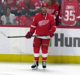 Mike Green of the Detroit Red Wings stands at the boards during pre-game warmups before their home opener against the Minnesota Wild.