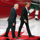 Detroit Red Wings greats Mickey Redmond and Nicklas Lidstrom walk off the ice after participating in a ceremonial faceoff.